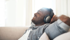 Cropped shot of a handsome young man relaxing at home with his headphones on