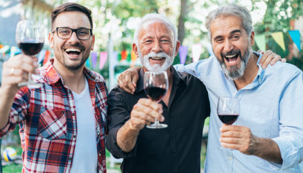 Happy three men drinking red wine outdoor on garden party